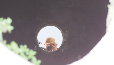 A man in a stylish hat photographs one of the many wells on Delos.